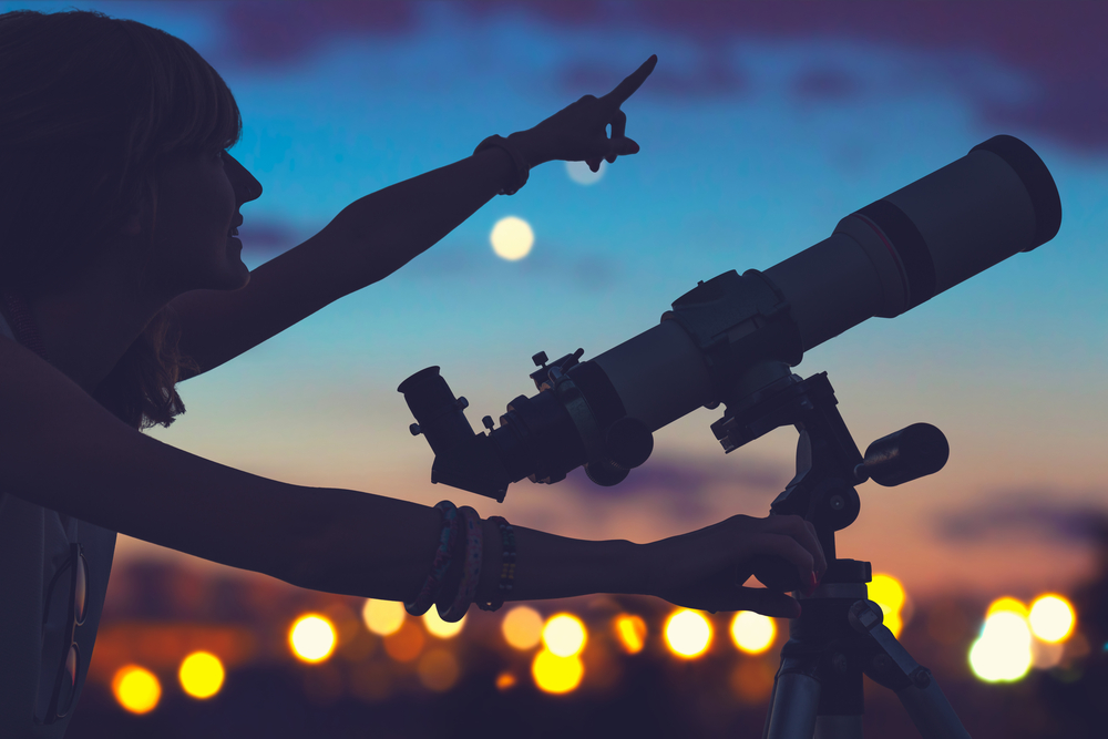Girl pointing at the starry sky with a telescope