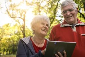 Man and a woman outside, smiling while on a tablet